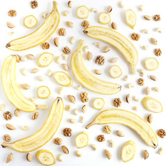Food pattern of fresh fruit and walnuts. Sliced bananas, walnuts, almonds on white background. Composition from fruits, top view, flat lay. The concept of healthy eating.