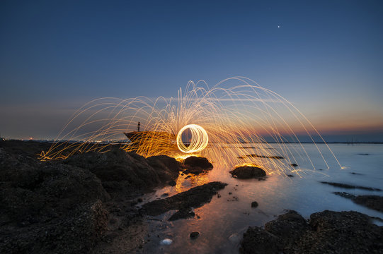 Showers of hot glowing sparks from spinning steel wool on the beach
