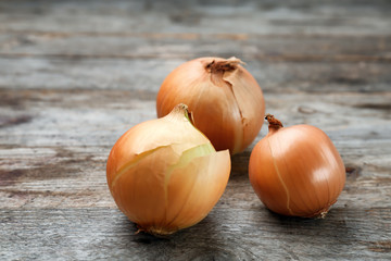 Fresh raw yellow onion on wooden background