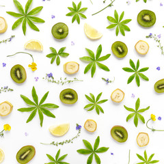 Composition of fruits and flowers. Fruit pattern. Plants and fruits on a white background. Slices of kiwi and bananas with green leaves and flowers. Top view, flat lay. Floral abstract background.
