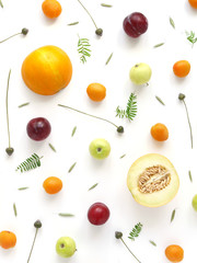 Composition of fruits and flowers. Fruit pattern. Plants and fruits on a white background. Melon in a cut, apricots, plums, apples with green leaves. Top view, flat lay. Floral abstract background.