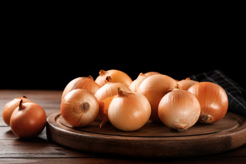 Board with fresh raw yellow onion on wooden table against dark background