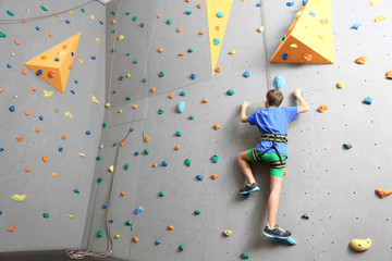 Young boy climbing wall in gym