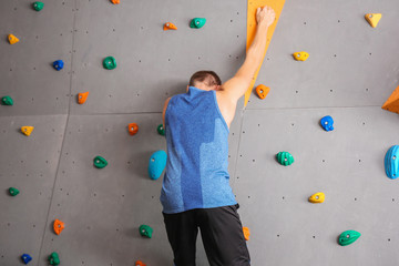 Young man climbing wall in gym