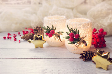 Christmas decoration- decorated candles,red berries,cones and golden stars on white wooden table