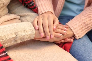 Senior woman and young caregiver holding hands, closeup