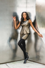 African American Business Woman Fashion in New York. Lady wearing metal crystal sleeveless mini dress top, skit suit, black leggings, high heels, stands against silver metal wall, looking forward..