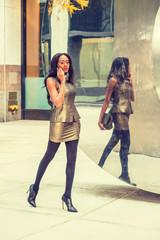 African American Business Woman travels, works in New York, wearing metal crystal sleeveless mini dress top, skit, leggings, heels, carrying bag, walks by metal mirror on street, talks on cell phone..