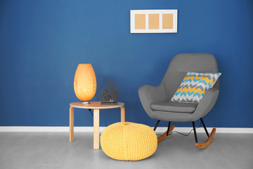 Modern interior with rocking armchair on blue wall background
