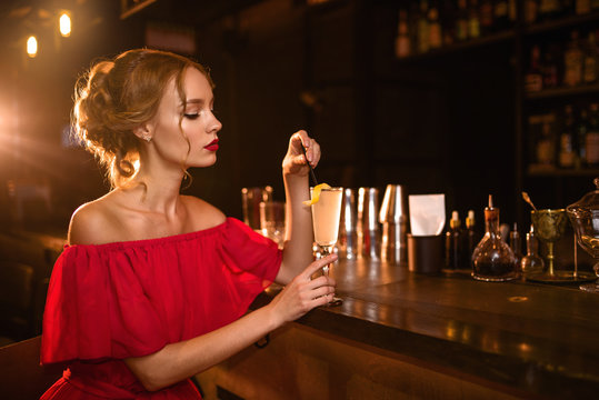 Woman in red dress drinks cocktail at bar counter