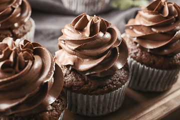 Tasty chocolate cupcakes on wooden board