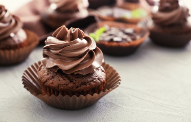 Tasty chocolate cupcake on textured background