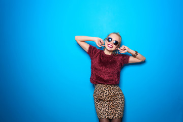 Attractive hipster girl with sunglasses on color background