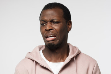 Disguting! Shocked young african american man looking at something unpleasant and bad, isolated on gray background. Negative emotion concept