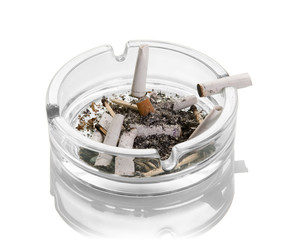 Cigarette butts, ashes, burnt matches in a glass ashtray isolated on white. Close-up