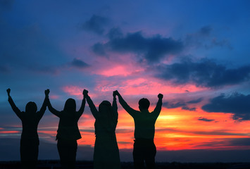Silhouette of happy business team hold hands up in sunset sky background, business teamwork, business achievement  conceptual