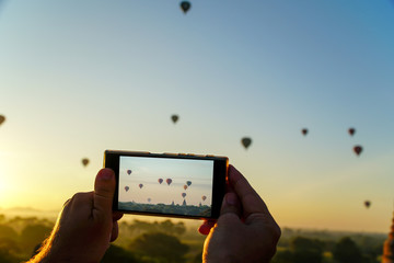 Taking Mobile Photos of Hot Air Balloons in Bagan. Active trip to Myanmar