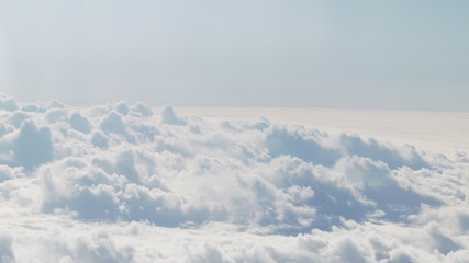 aerial shot from plane flying above the clouds in daytime