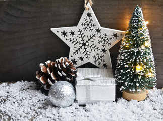 Christmas decoration with fir tree, garland lights,gift box,and glittering christmas ball on old wooden background.Winter holidays concept.Copy space.Selective focus.