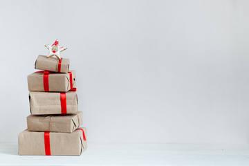 gift boxes made in a stack, wrap in kraft paper and a red ribbon with a star from the baking on top, copy space