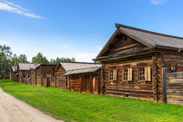 A wooden huts on the street of the Siberian village at summer. Architectural ethnographic Museum Taltsy on the shore of the Angara river near lake Baikal