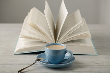 Coffee in a light blue cup and book in blue cover on a wooden background.