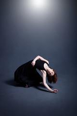 Dancer in a black dress is dancing in the dark studio