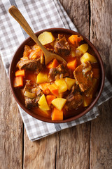 delicious stew estofado with beef and vegetables close-up. Vertical top view