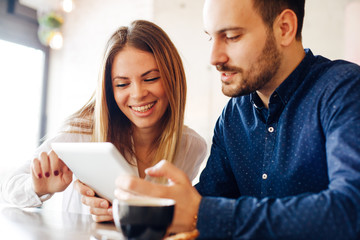 Young couple having fun in cafe with digital tablet