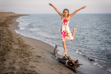 Happy little girl standing on the tree on the beach