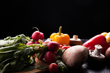 Delicious fresh vegetable on dark wooden background in close up image