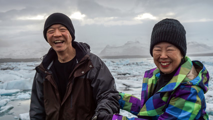 Asian senior couple fun trip in Iceland, majestic glacier lagoon landscape