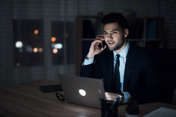 A man is sitting at a laptop in a dark office. The man in the suit works until late.