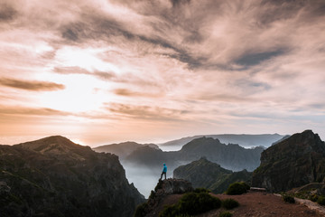 Adult male hiker in blue jacket watching the dramatic sunset on top of a Mountain in Madeira, Portugal
