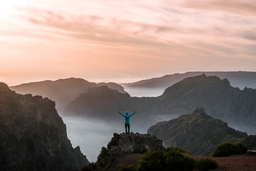 Adult male hiker celebrating the sunset over the mountain panorama of Madeira, Portugal