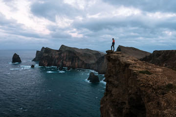 Adult male standing over the rocky ocean cliffs of Madeira, Portugal with dramatic sky during evening blue hour