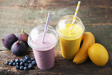 Wall Mural - Sweet smoothie in plastic cups with fruits on wooden table