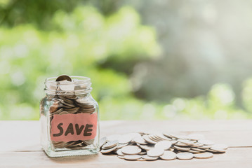 Coins in glass jar for money saving with natural sunlight in background .Saving money financial concept
