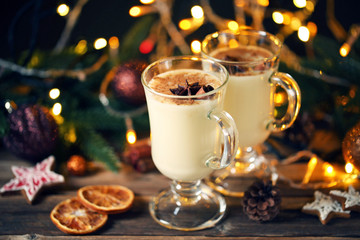 Eggnog in glasses with cinamon and star anise on wooden table