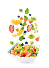 Sliced fruits falling into bowl with salad on white background