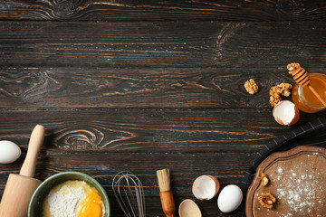 Kitchen utensils and food ingredients on wooden background