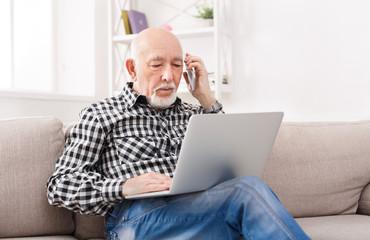 Senior man talking on phone with laptop