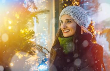 Frau schaut in ein Laden Schaufenster an Weihnachten