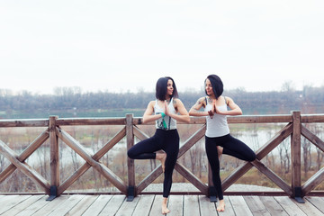 Two attractive sport women twins work out tree yoga pose on black mat outdoors on nature. Group of young women stretching on wooden bridge on spring park