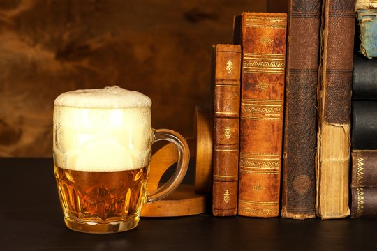 Glass of cold beer and old books. Rest with the book.