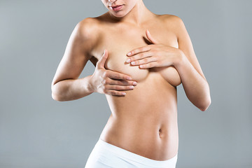 Young woman performing a breast self-examination over gray background.