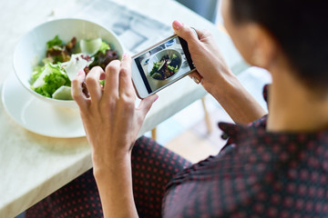 Close up of unrecognizable woman taking photos of food in cafe, focus on salad bowl in smartphone screen