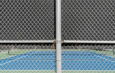 Tennis court chain link fence poles. Blurred blue and green painted concrete court in background.