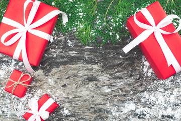 Set of red gift boxes with ribbon and rope bow with decorated element on old and rustic wooden background and snow.