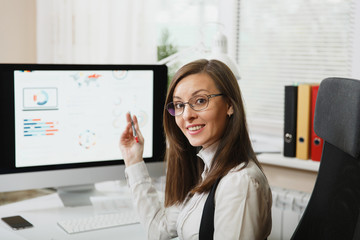 Beautiful smiling brown-hair business woman in suit and glasses working at computer with documents in light office, looking at the camera, against the background of the monitor, close up.